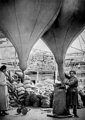 Black and white photo of two women filling bags of asbestos in a factory
