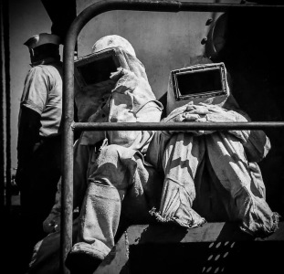 Black and white photo of Navy firefighters in asbestos suits