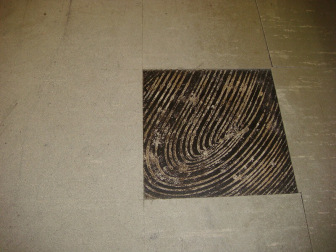 Square floor tile with asbestos and trowel marks