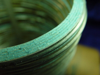 Close-up surface-view of fibrous asbestos insulation material in a vintage Flexitallic spiral-wound gasket