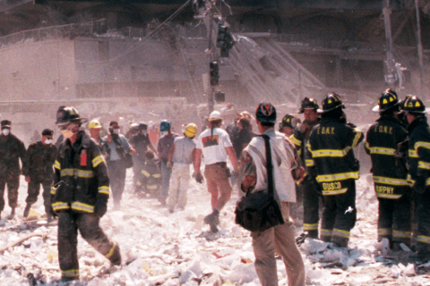 First responders standing among debris at