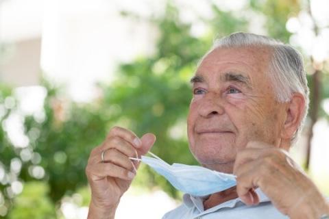 Older man taking off medical mask