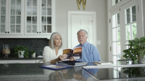 Couple reading asbestos cancer book in kitchen