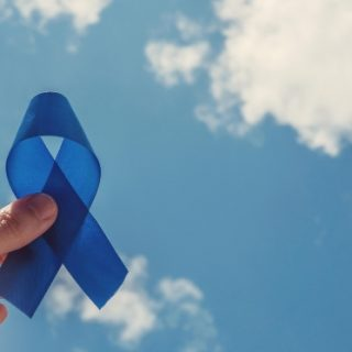Man holding blue ribbon up to the sky
