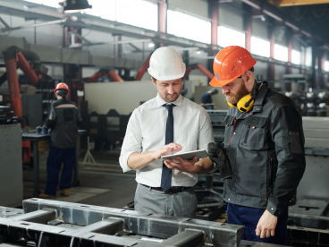 Two men in hard hats in manufacturing plant