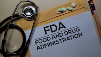 Stethoscope and a folder of FDA documents with prescription pills