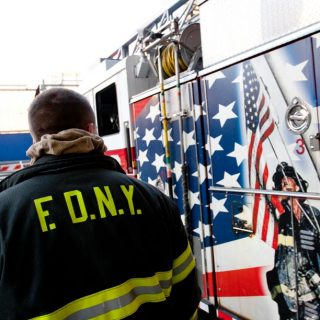 FDNY firefighter looking at 9/11 memorial on fire truck