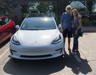 Jim and Kathy Huff with their white Tesla