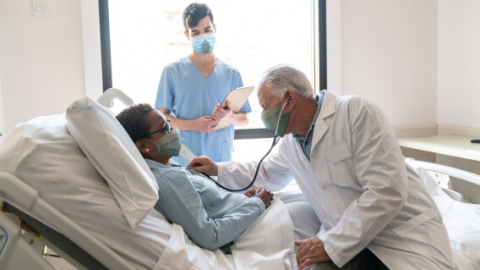 Patient in hospital bed with doctor and nurse
