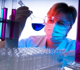 Female researcher examines flask with blue fluid