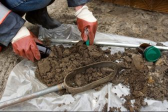 Gloved person with soil samples on tarp