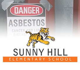 Sunny Hill Elementary mascot with asbestos sign
