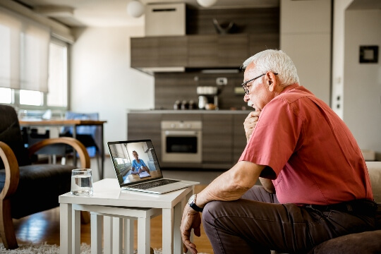 Older man looking at computer with image of doctor