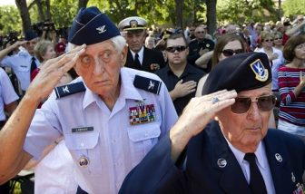 Two U.S. Air Force veterans saluting in a crowd