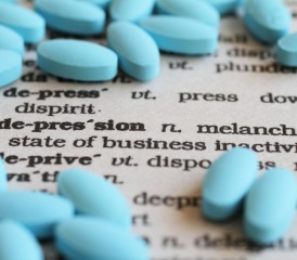 Blue antidepressant pills on a dictionary