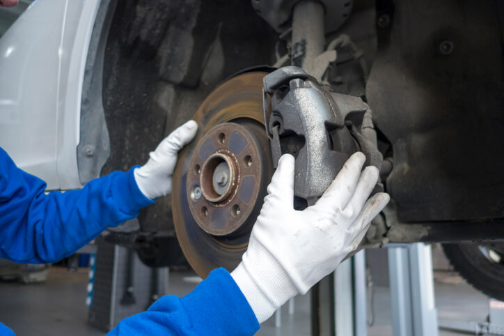 Auto mechanic handling an asbestos brake pad