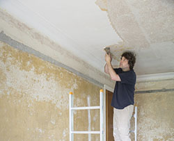Homeowner scraping popcorn ceiling texture in a house