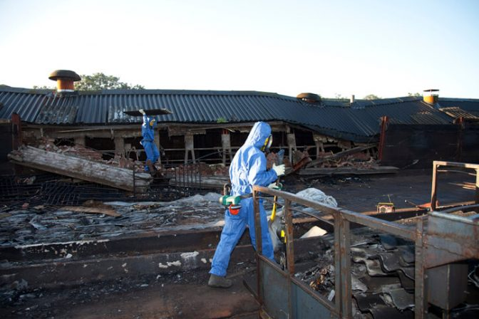 Workers removing asbestos from a demolition job