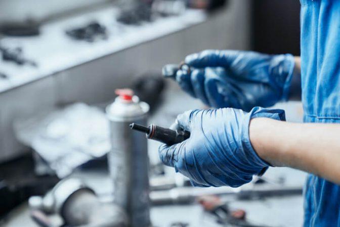 Auto mechanic holding a spark plug