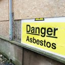 Asbestos warning on boarded up building