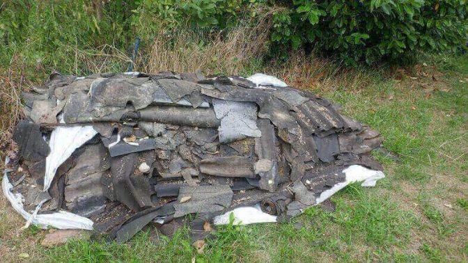 Shingles and waste materials from a home remodel dumped in a ditch