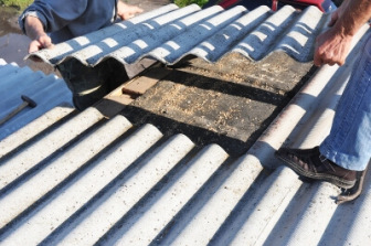 Workers remove asbestos roofing