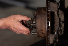 Man's hand fixing the brakes of a car