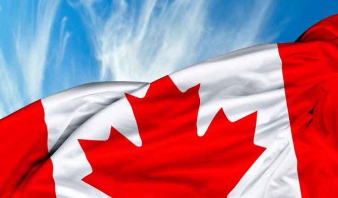 Canada flag waving against sky