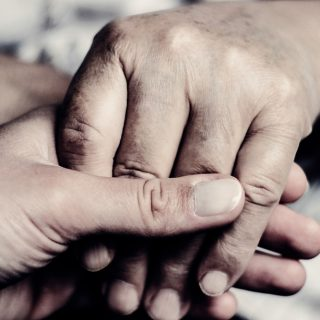 Caregiver holding hand of patient