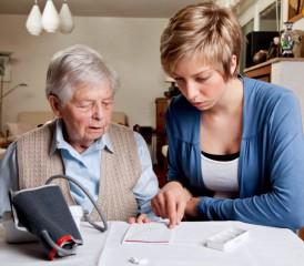 Caregiver helping patient with medicine