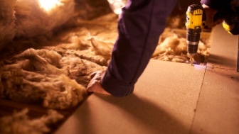 Carpenter in attic with old insulation
