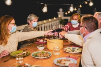Group with masks toasting over food outdoors