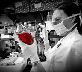 Female researcher holding bottle with red liquid