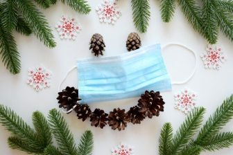 medical mask with snowflakes, pine cones and fir branches