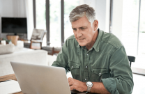 Older man viewing webinar on a laptop