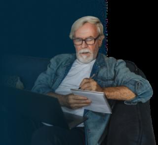 Elderly man taking notes during a webinar.