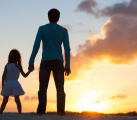 Daughter with her father looking at the sunset