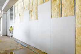 Man installing drywall in a warehouse