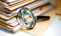 stack of file folders with magnifying glass