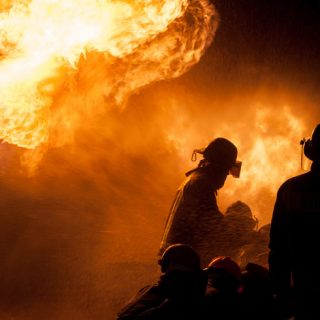 Silhouette of firefighters against a blaze