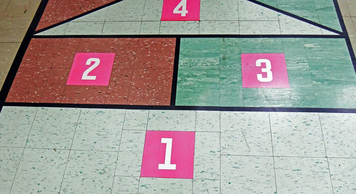 Asbestos-containing floor tile being used as a hopscotch game in an elementary school.