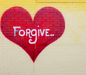 Red heart labeled with forgiveness and painted on a wall