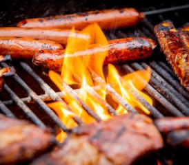 Meats and hot dogs grilling over an open flame.
