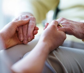 A person holding another person's hands in a consoling manner