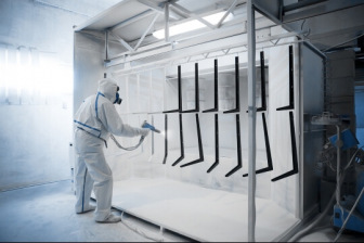 Industrial painter in white protective gear