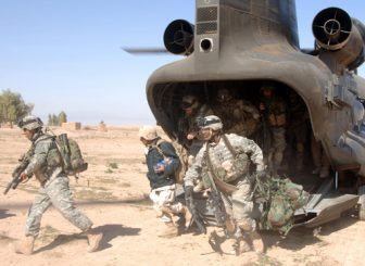 U.S. Soldiers running out of a CH-47 Chinook helicopter during the Iraq war.