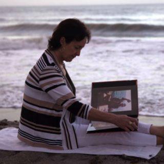 Lorraine Kember on the beach with photo album