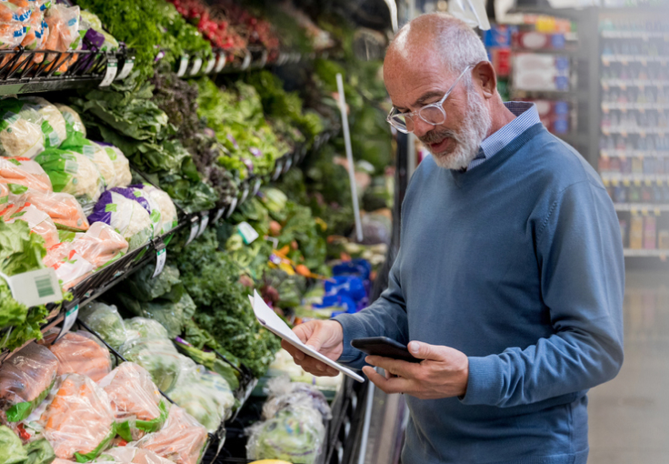 Older man shopping for vegetables in a grocery store