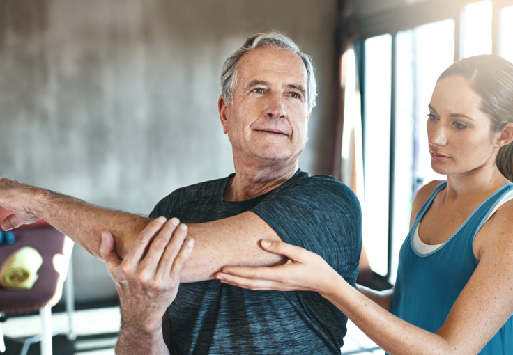 Older man stretching with a personal trainer in a gym
