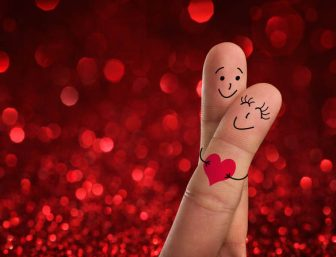 Fingers painted with happy faces in love